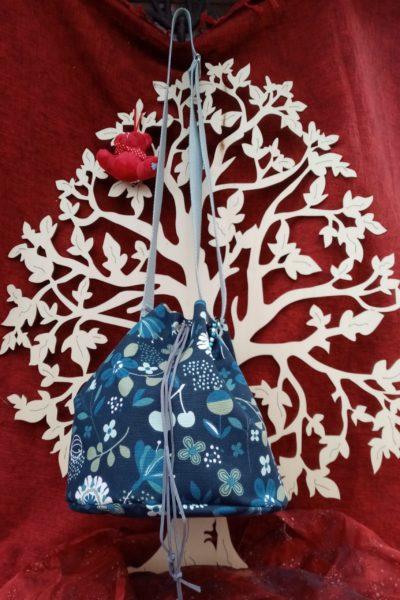 Sac sceau motifs fleurs et fruits verts et bleus sur fond bleu foncé. Fond rigide de 25cm de diamètre et sac de 24cm de hauteur. Sangle grise réglable. Fermeture par un lacet qui passent dans des œillets métalliques et qui se ferme par un stop cordon. Petites décoration en perle latérale. Cherchez le Chas