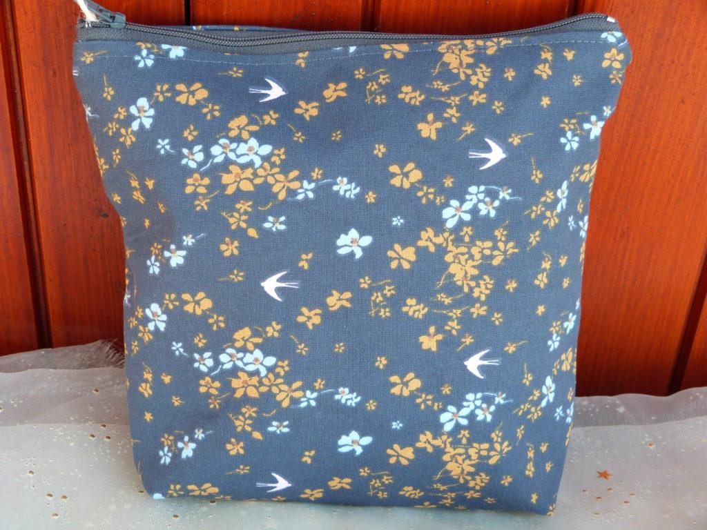 Trousse à motifs fleurs jaunes et bleu clairs avec des petits oiseaux, sur fond gris anthracite, intérieur bleu clair. Coton extérieur renforcé, intérieur cretonne de coton unie. Fermeture éclair. 20cm de haut 20cm de large, et 5cm de profondeur. Cherchez le Chas
