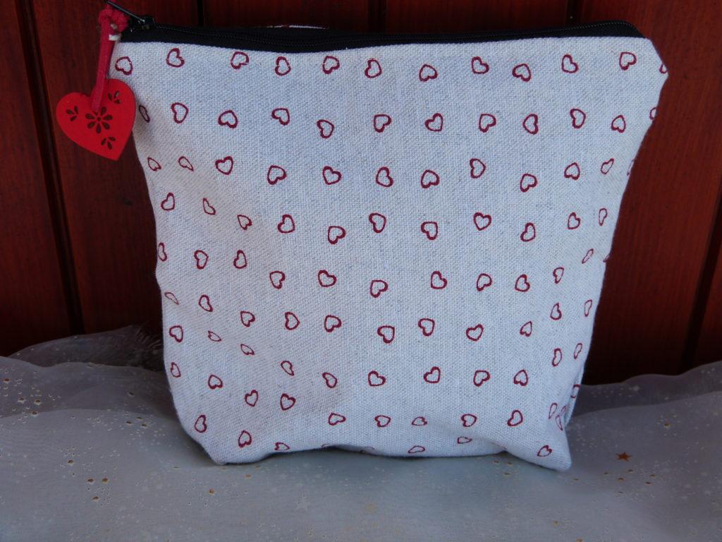 Trousse à motifs coeurs rouges sur fond écru, intérieur rouge. Coton extérieur renforcé, intérieur cretonne de coton unie. Fermeture éclair avec une petit déco coeur accrochée dessus. 20cm de haut 20cm de large, et 5cm de profondeur. Cherchez le Chas